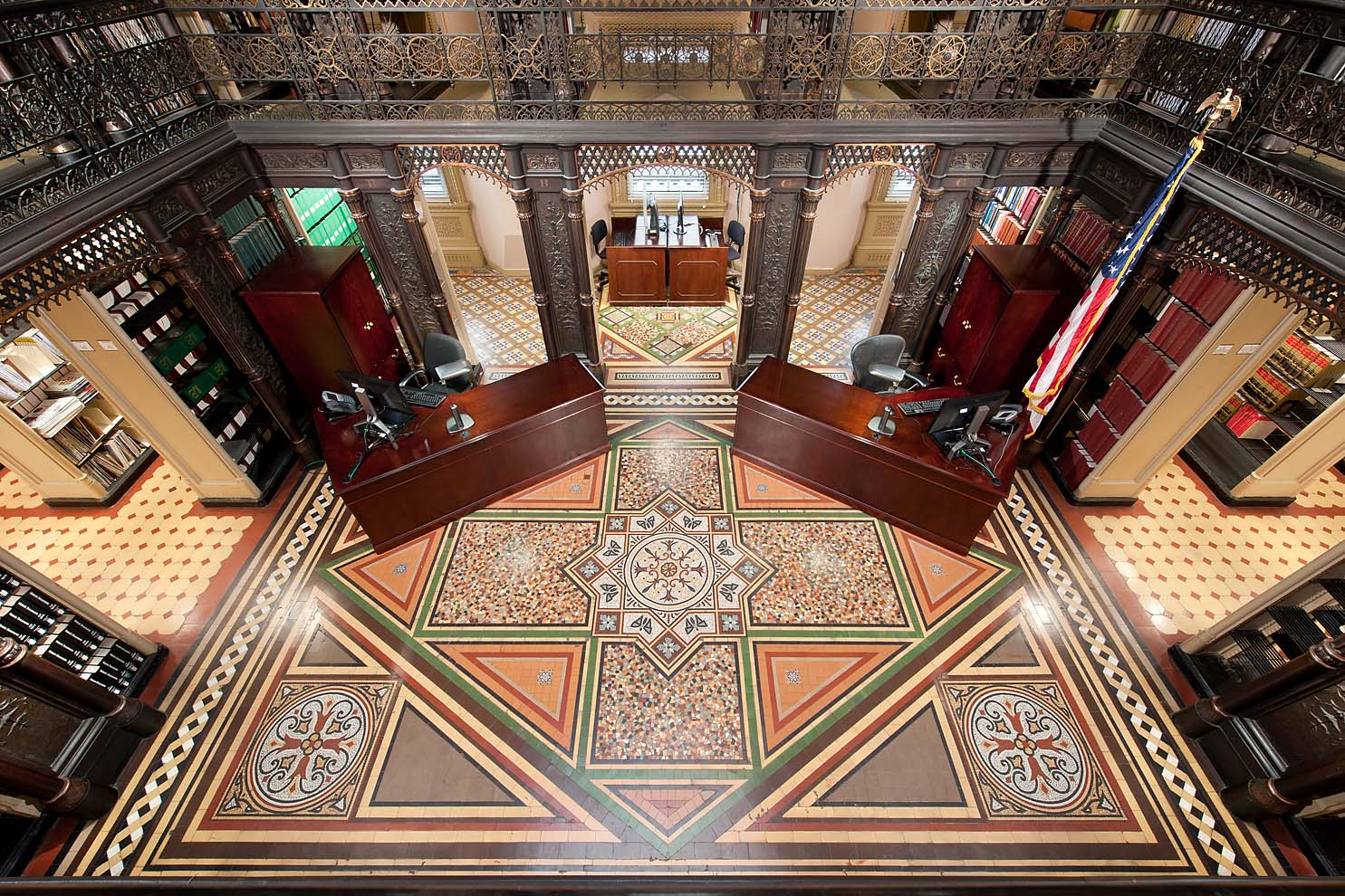 looking down to patterned tile floor and cast iron ornamental railings
