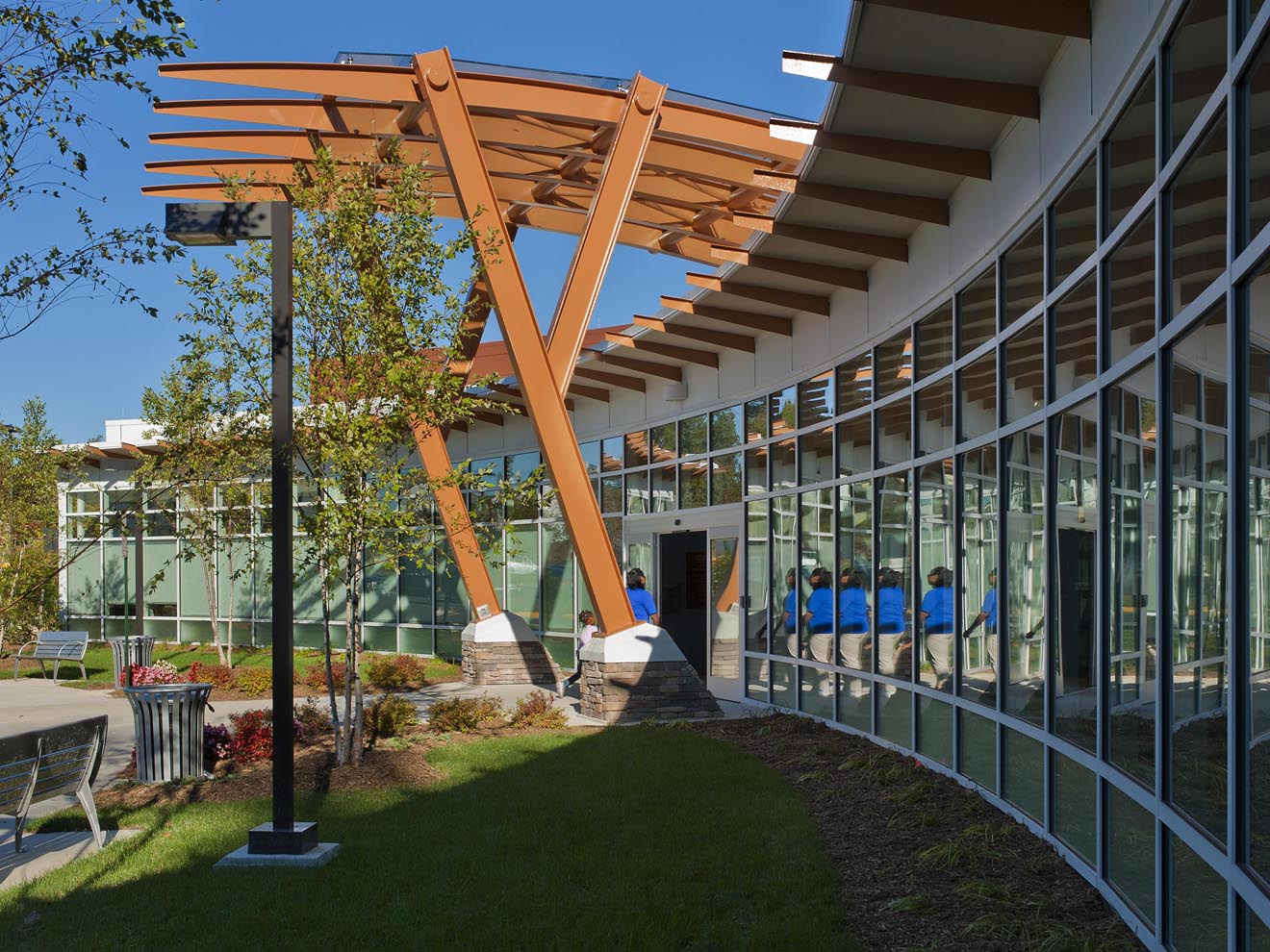 person entering library entrance under canopy during daytime