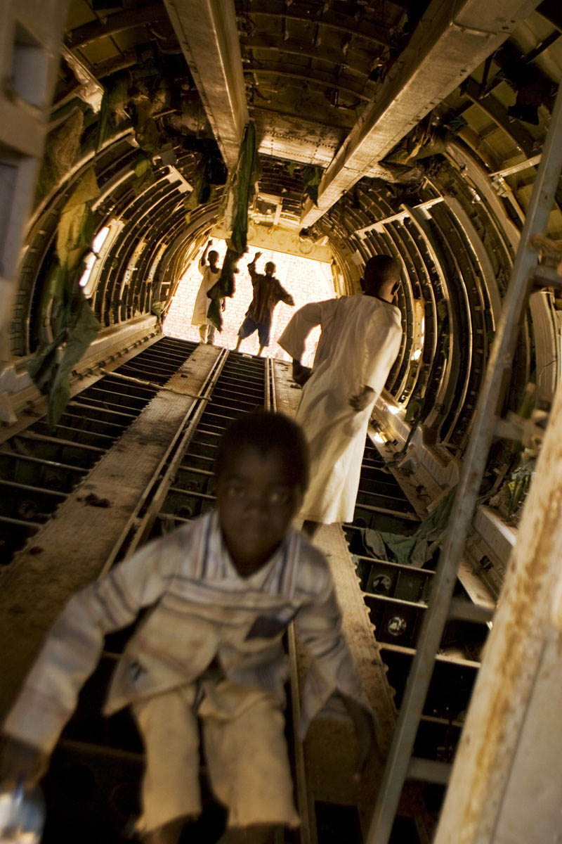 "Children play in the fuselage of a crashed Sudan Armed Forces Antonov bomber.  A local resident remarked on the plane, ""During the war this plane came and killed many people - then it died here.""Raja, Western Bahr el Ghazal State"