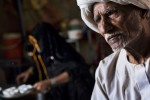 A Rashaida elder sits in his home while his wife prepares coffee.Malamiye, Kassala State