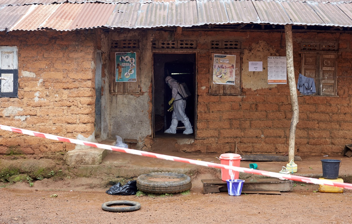 A decontamination worker (student nurse) cleans the house after a gentleman died from Ebola in the home. Tonkolili, Sierra Leone