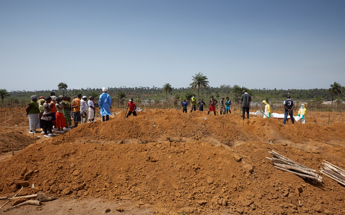 Families & workers are kept at a safe distance as an Ebola victim is buried in a safe and dignified manner. Waterloo, Sierra Leone
