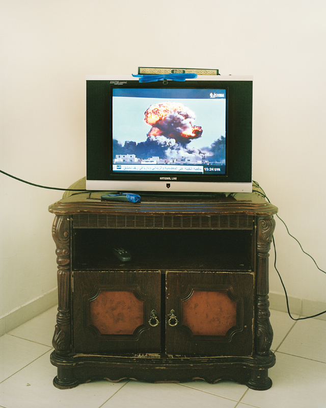 A TV in the apartment shared by Abdul Rahman's three sisters is tuned to a Free Syrian Army channel showing a neighborhood being bombed.