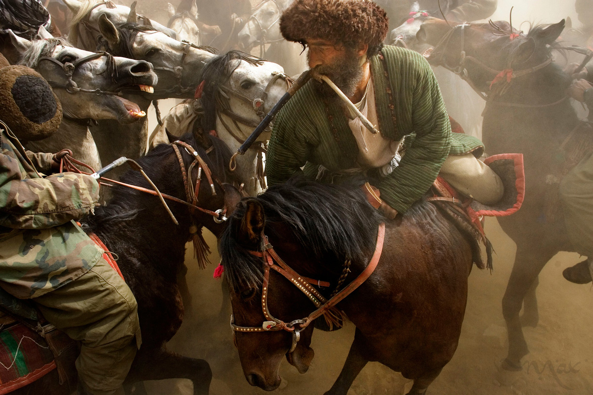 Khenj, Afghanistan: With the sound of whinnying horses and whips, a horsemen with his whip in his mouth tries to reach down from his horse to reach down to the ground from his horse and pick up the carcass of a dead calf. On Friday, October 26, 2007 in a rare respite from the rigors of their work in the emerald mines in the mountains high over their village or from workshops and business, the men of Khenj, Afghanistan, compete in a game of Buzkashi.