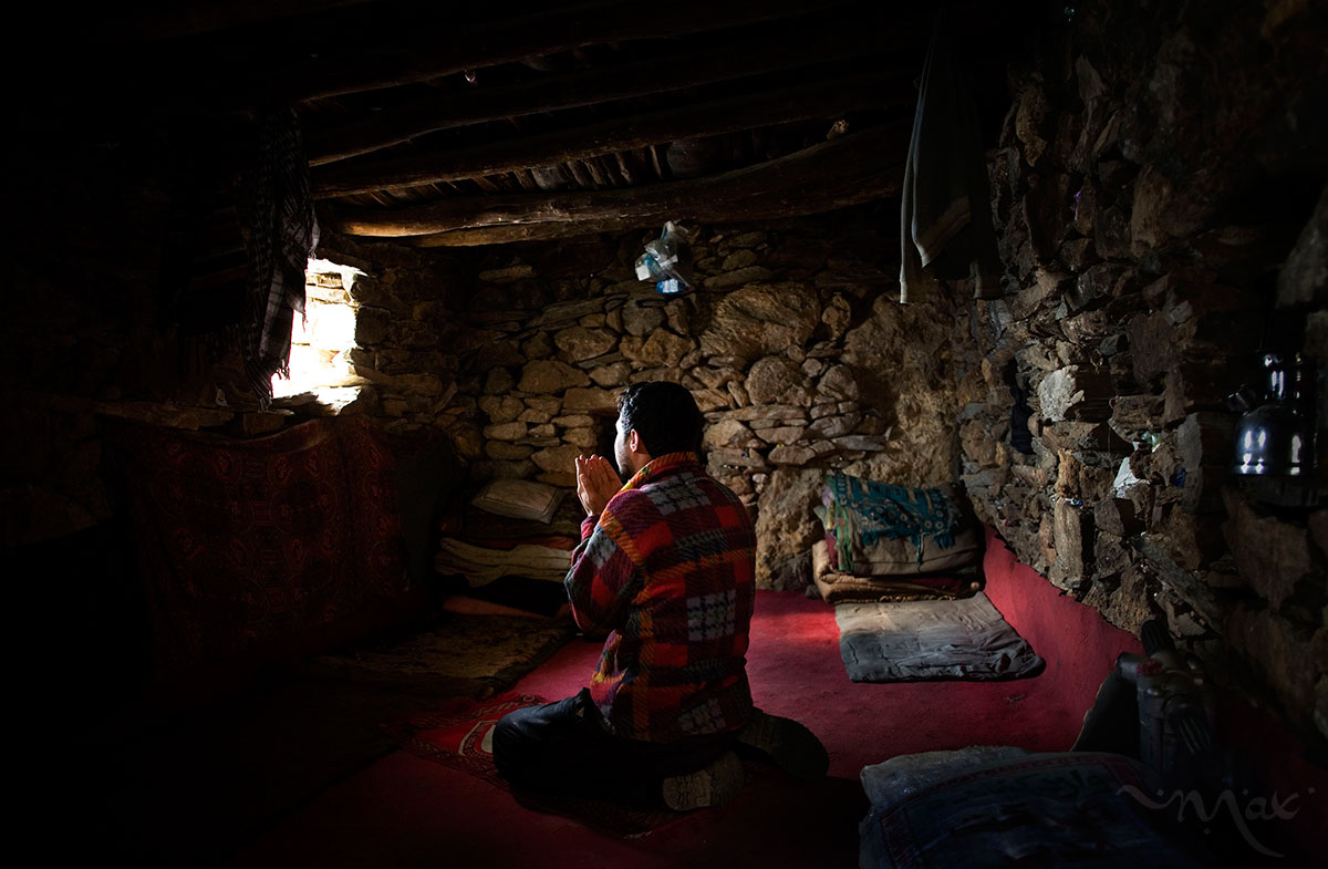 "October 25, 2007- Khenj, Afghanistan: Burhan Amin, 26, prays in the one room stone he shares with the rest of his team of miners in the slope of the Hindu Kush mountains towering over the Panjshir Valley near the village of Khenj, in Afghanistan on Thursday October 25, 2007. Burhan Amin, 26, a partner and cousin of Mr. Jawead, has a kidney ailment that does not allow him to work, brought on from years of battling the mountain for emeralds. Instead of maning the rock drill, Mr. Amin prepares the meals of rice, bread, lamb meat and tea for grime covered miners.  Even with this light duty, he sometimes feels too ill to work.  ""Most of the time I am sick. Those days when I am not feeling well, because there is the mountain and it is the work of the mountain. If we work from the morning till night, you will know how much you get tired,"" Mr. Amin said."
