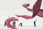 Red fabric dragons dance in the foreground with blurred Conemen standing on a beach in the background