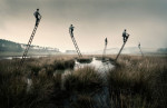 Laurence Winram Photography. Men on top of floating ladders in a misty landscape