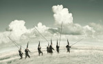 Several Conemen wander across an alien curved green landscape with big billious clouds in the sky. They each carry a long wooden pole.