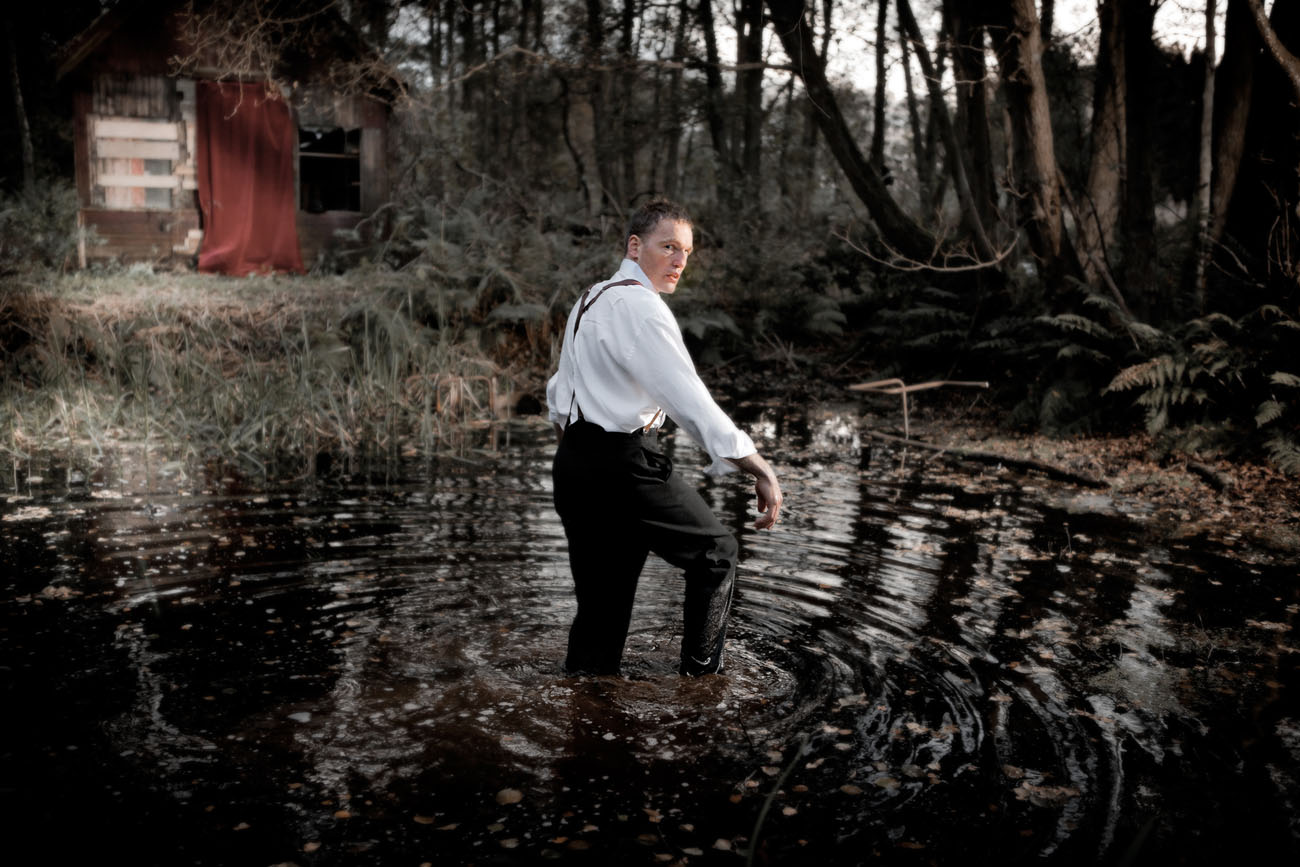 a man stands in a lake in a dark forest turned looking back