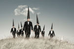 seven Conemen stride across a grassy landscape with black suits and black pointed hats