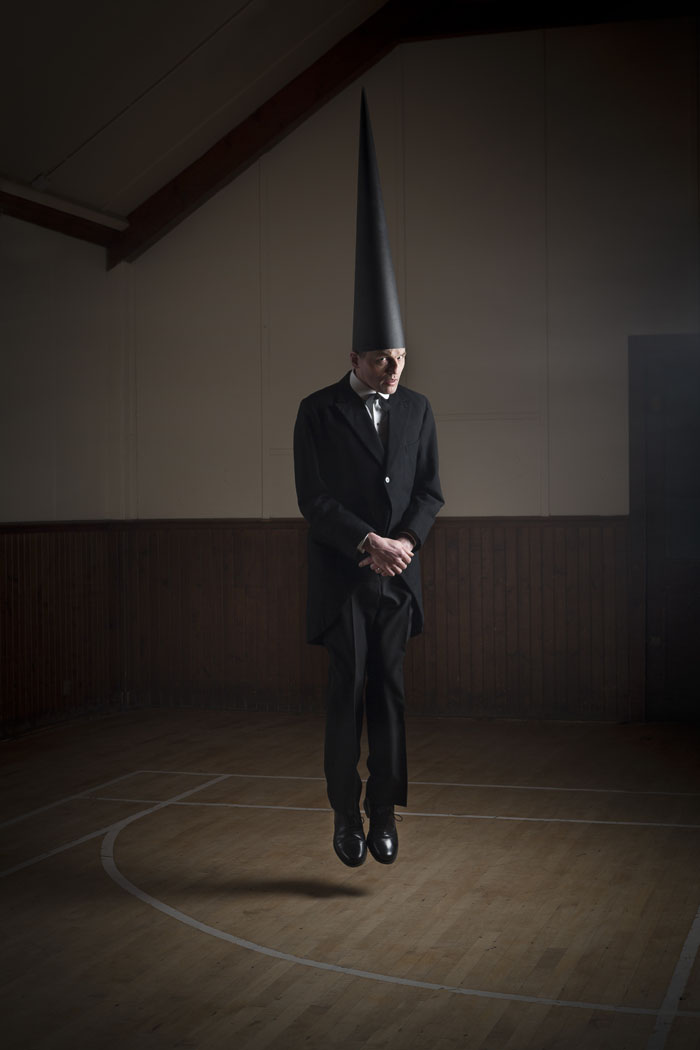 A conemen floats in a dark hall staring at the viewer. He wears black tails and a pointed black hat
