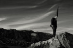 A lone coneman in a black suit and black pointed hat stands on a rocky outcrop with beautiful cirrus clouds in the sky behind. Black and white landscape photograph.