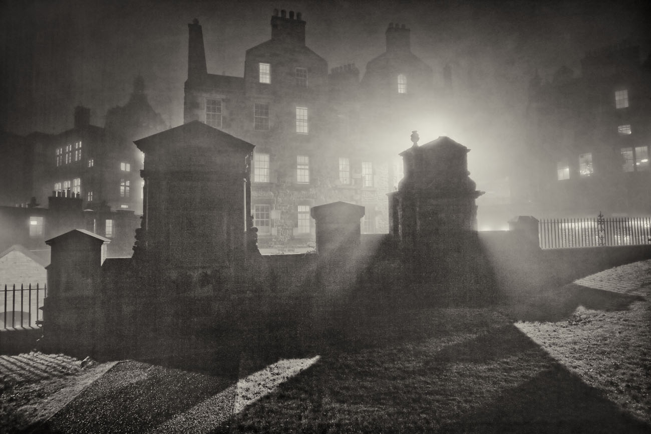 light filtering through the fog onto gravestones in Greyfriars Kirk at night.