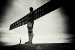 A coneman stands at the foot of the angel of the north with a feather in his hand. It's a stormy day and the photograph is black and white.