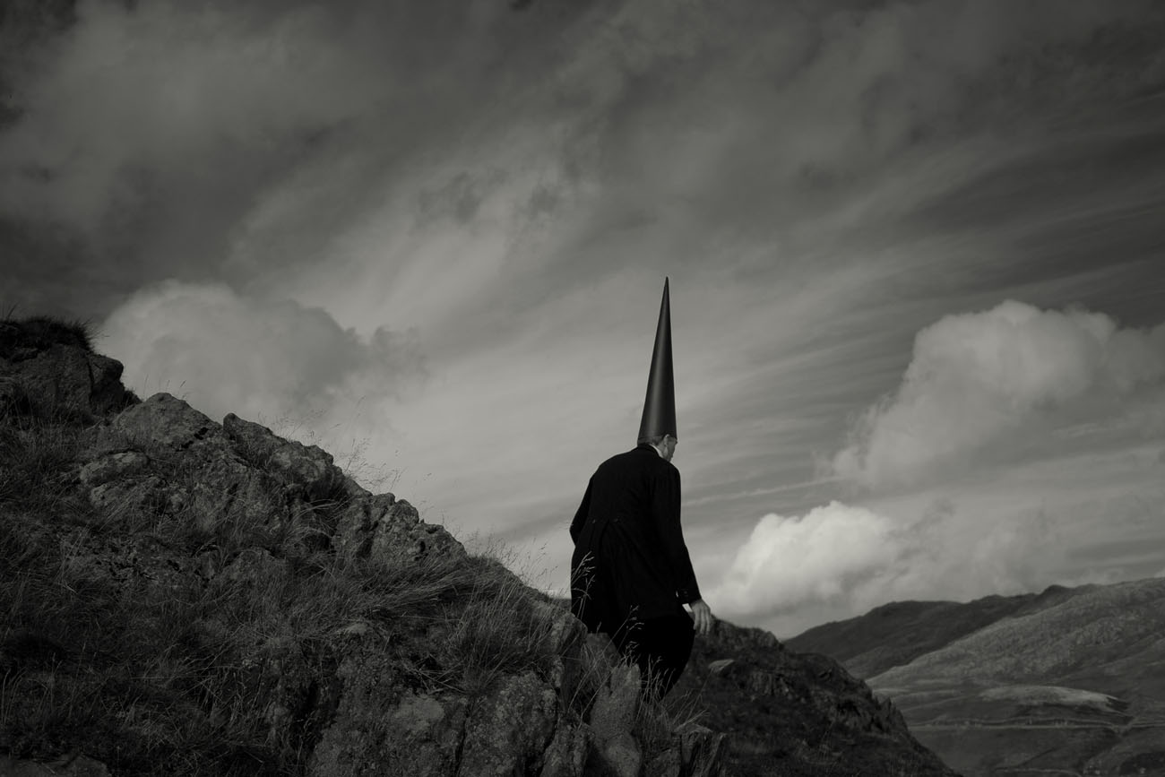 a lone Coneman sitting on a stone in a country landscape. Black and white fine art photo
