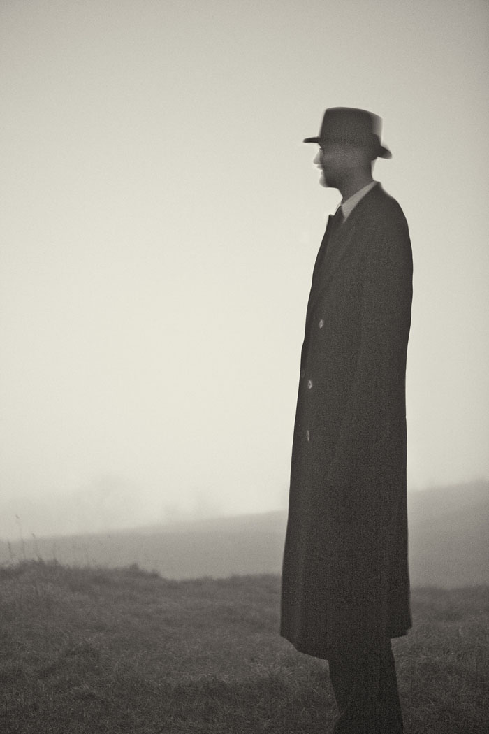 lone figure in a long coat and hat in a misty environment at night
