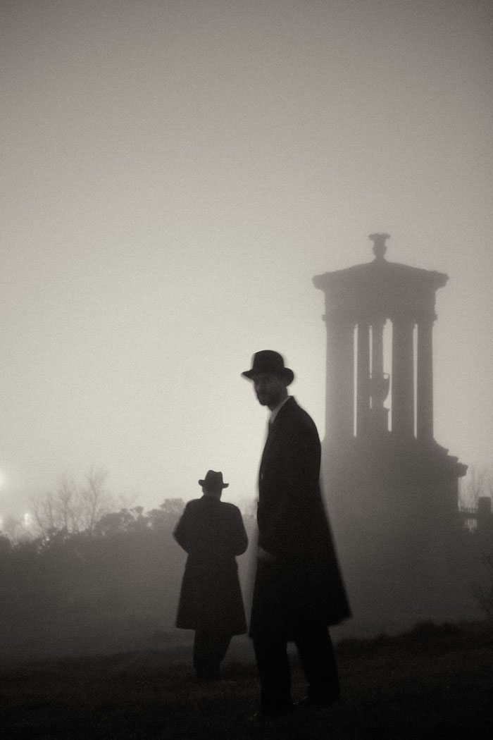 two men in long coats and hats in the mist onCalton Hill at night