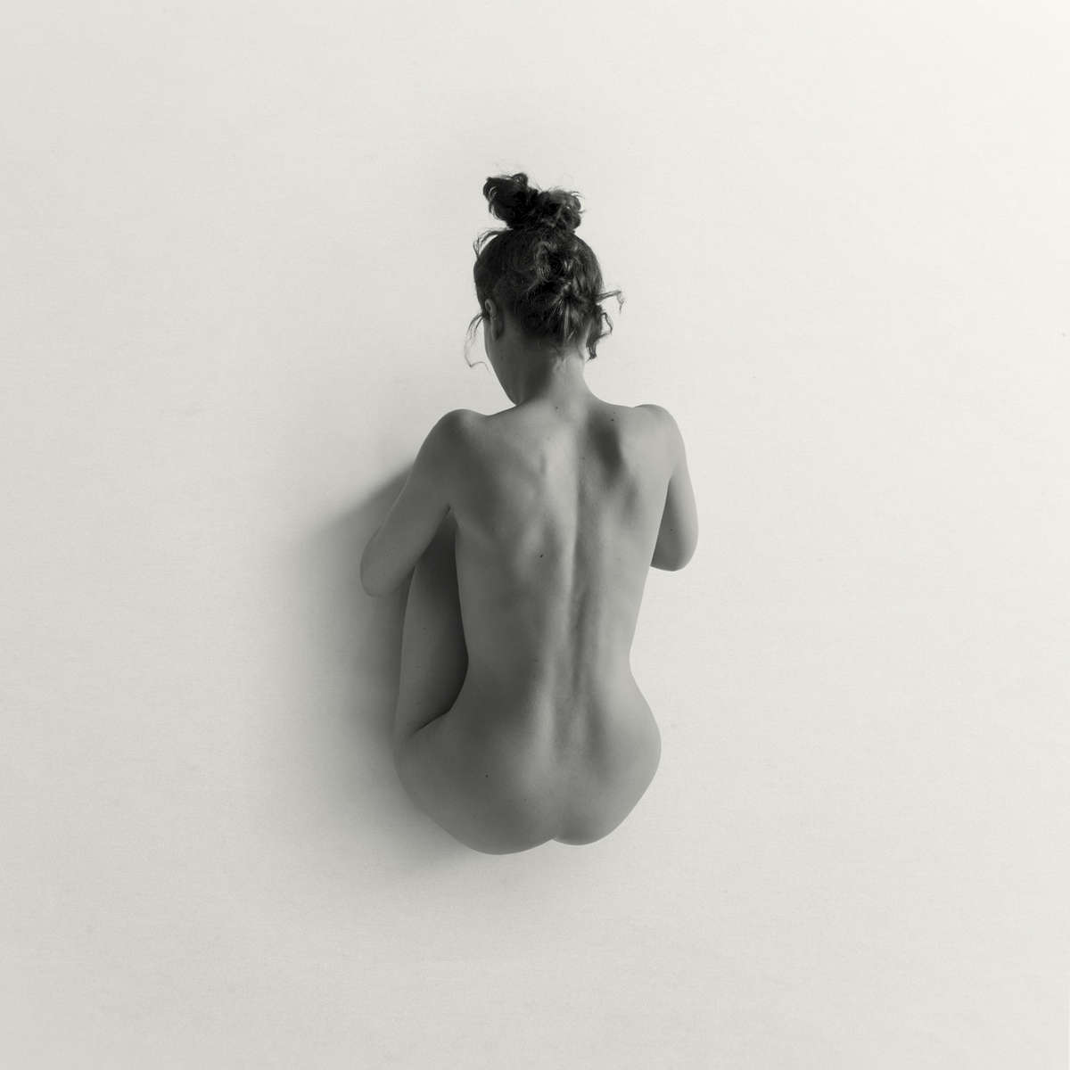 crouching nude woman on white in a studio