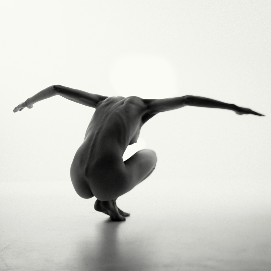 crouching shadowed nude girl with arms outstretched like a bird