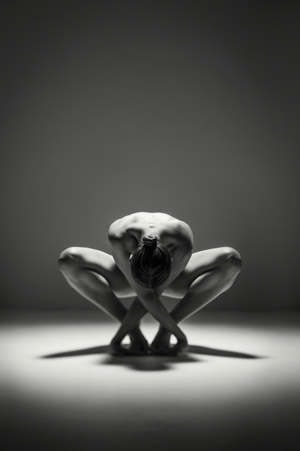 crouching nude figure of a woman in a dark studio. Spotlit naked girl in black and white
