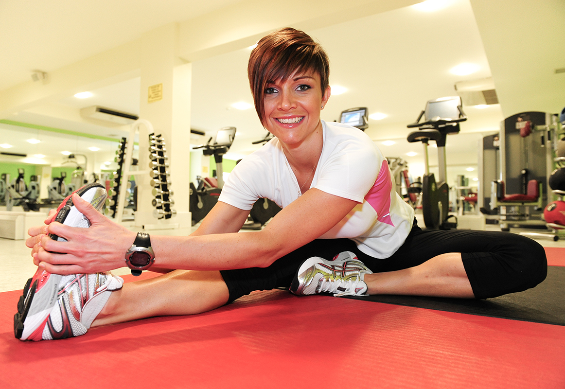 Colour portrait of a female personal trainer in the gym. She is stretching her leg and smiling looking towards the camera.