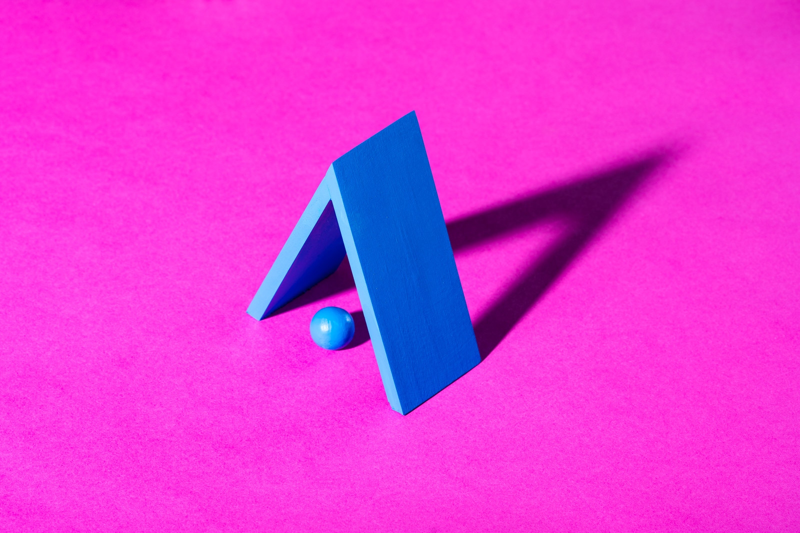 Blue recreation of the Nutrafol logo on hot pink paper. Nutrafol hair loss product photography by Reciprocity Studio photographers in Burlington, Vermont.