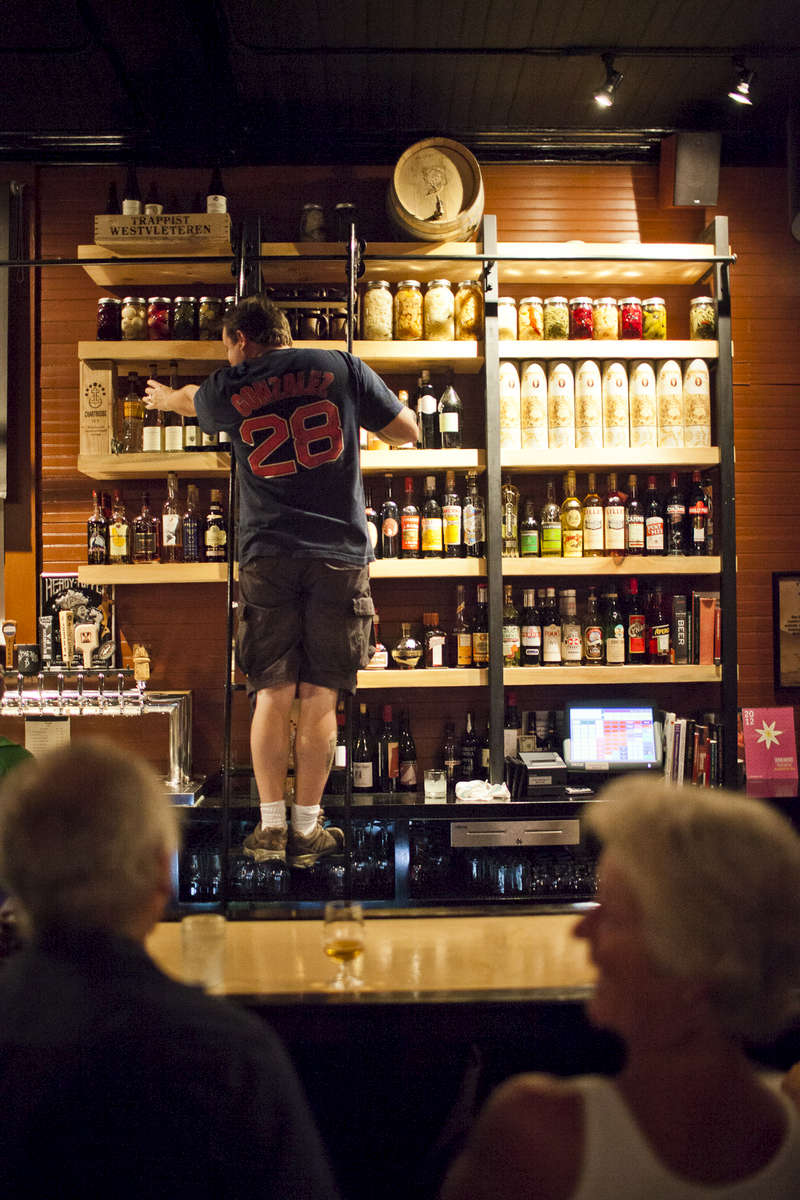 A bartender retrieves top shelf liquor at Prohibition Pig in Waterbury, Vermont.