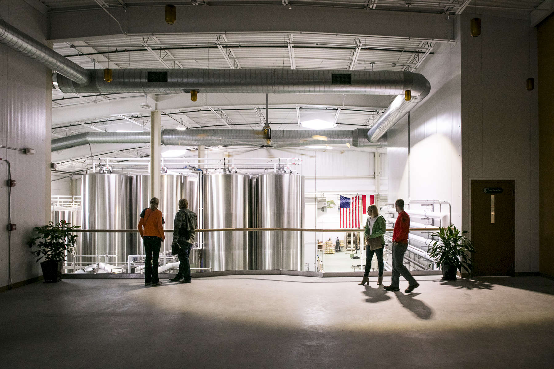 Tourists and beer nerds alike stand in front of massive brewery tanks in Vermont.