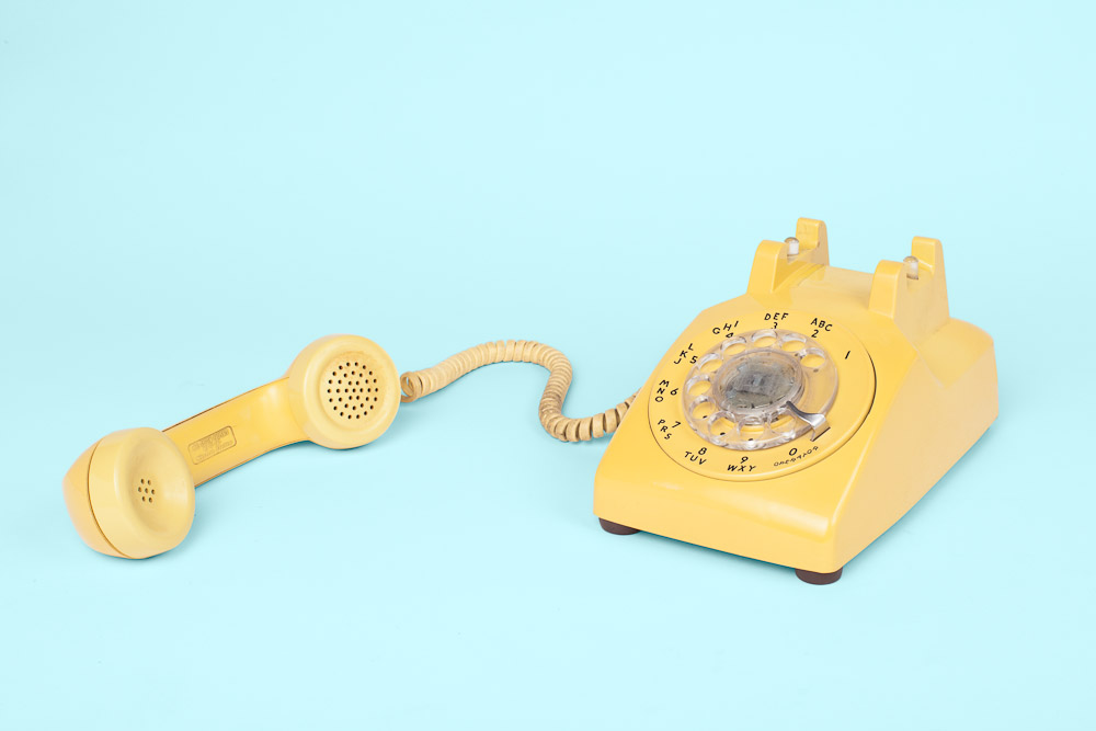 Yellow rotary dial analog vintage phone off the hook shot in studio by Vermont photographers Reciprocity Studio in Burlington.