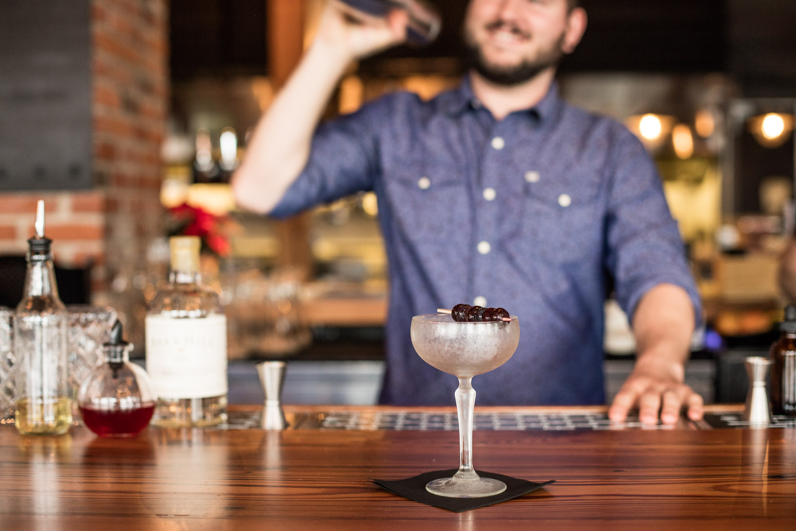 Caledonia Spirits cocktails and ingredients on the bar as a bartender makes drinks at Waterworks in Winooski, Vermont. by Reciprocity Studio for Caledonia Spirits.