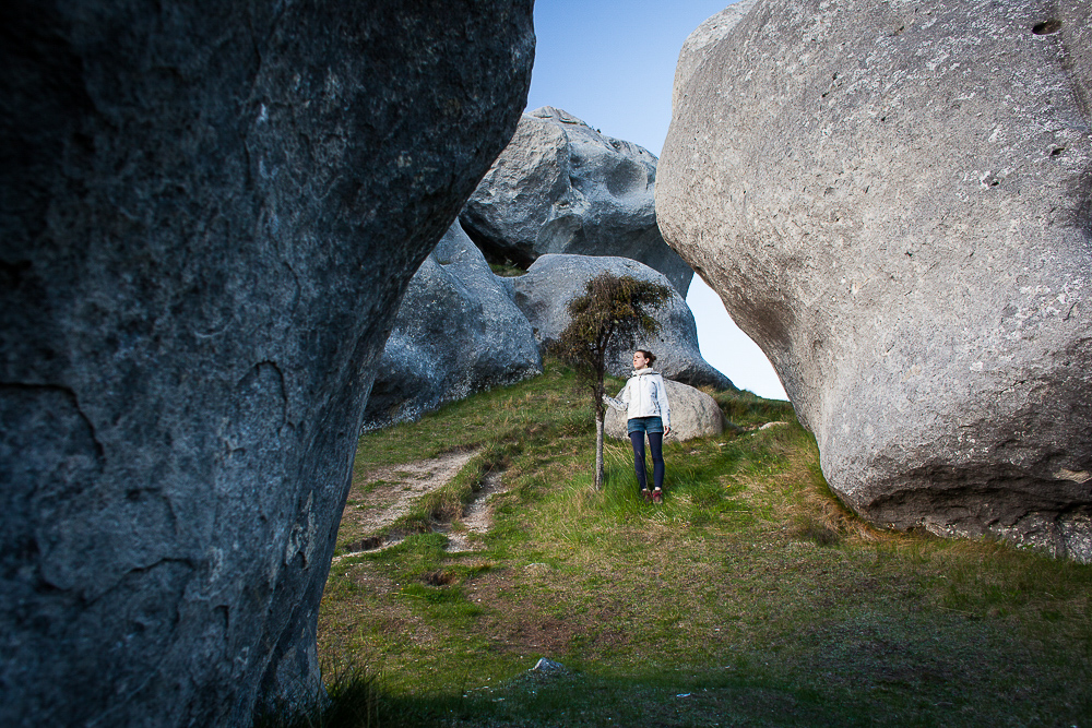 Young woman hiking through boulders in Arthur's Pass, New Zealand. by Vermont photographers at Reciprocity Studio, Burlington