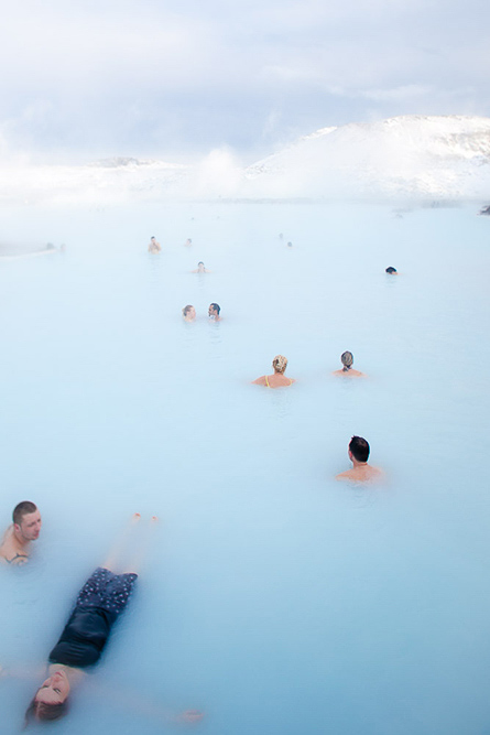 Many people swimming and relaxing in the Blue Lagoon, a geothermal spa fed by water products from the nearby Svartsengi geothermal plant. by Vermont photographers at Reciprocity Studio, Burlington