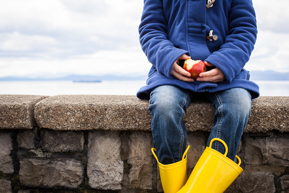 Young girl holding apple while wearing rain boots, with lake Champlain in the background. by Vermont photographers at Reciprocity Studio, Burlington