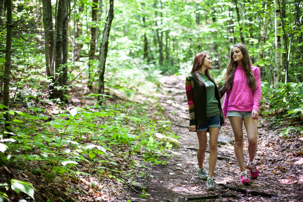 Two young women walking through forest. by Vermont photographers at Reciprocity Studio, Burlington