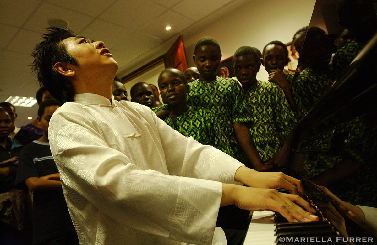 Children from the Dogodogo centre for street children look on as Lang Lang, UNICEF's newest and youngest Goodwill Ambassador and acclaimed classical pianist, plays the piano during a reception at hosted by UNICEF.This is Lang Lang's first visit as a UNICEF Goodwill Ambassador. His visit to Tanzania is to raise awareness about the impact of malaria and other diseases on children.