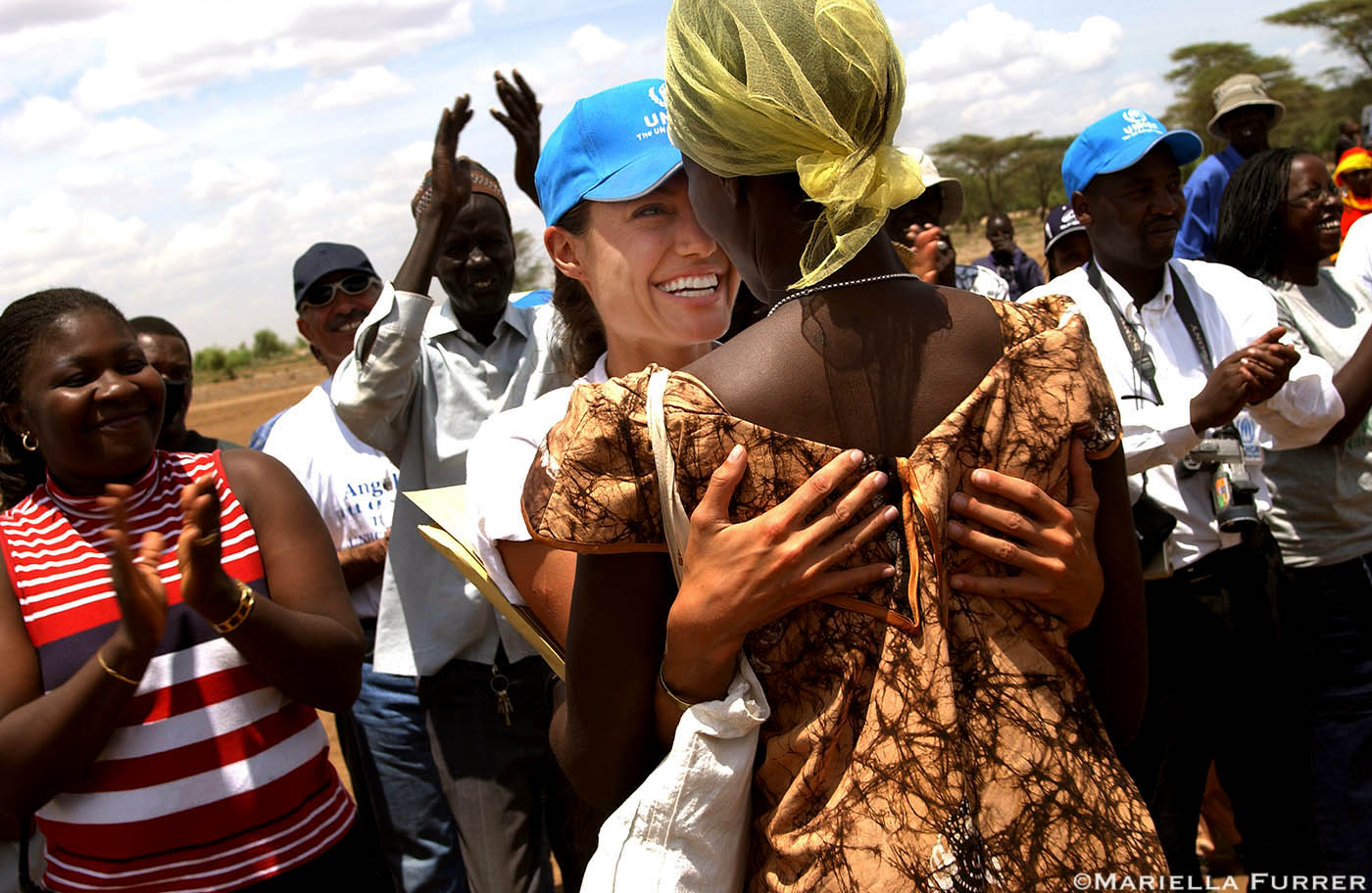 A refugee woman hugs Angelina Jolie, UNHCR Goodwill Ambassador, after a UNHCR official announces that she has given a donation so that the construction of a woman's centre can begin straight away. (**The woman is incharge of the centre to be built I think**). Kakuma refugee camp, Northern Kenya.