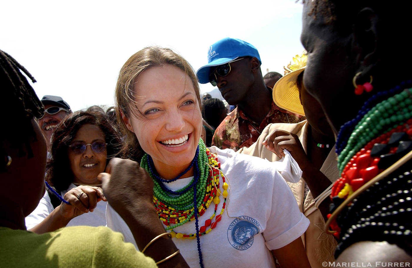 Angelina Jolie, UNHCR Goodwill Ambassador, gets help in putting on beaded necklaces given to her as a gift from a group of Pokot women (Kenyan Tribe) on her arrival at Kakuma refugee camp, Northern Kenya.
