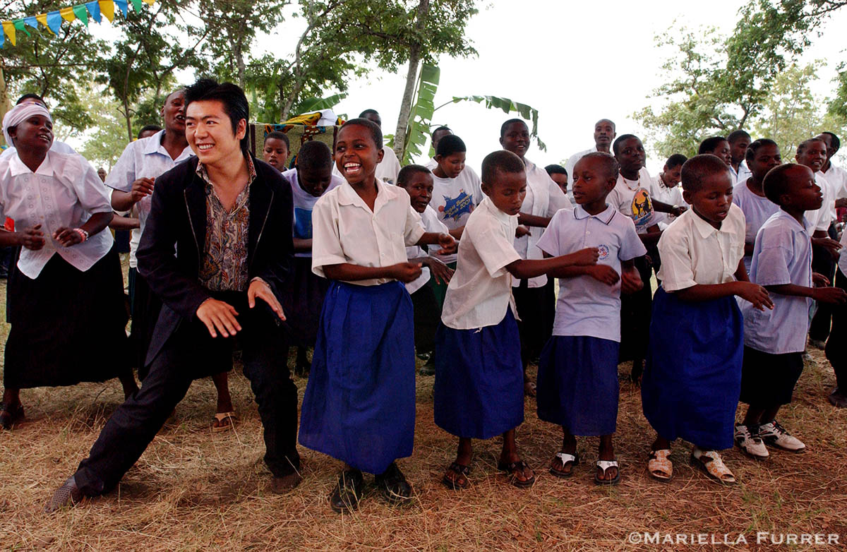 Lang Lang, UNICEF's newest and youngest Goodwill Ambassador and acclaimed classical pianist, dances with a group of school girls at a ceremony welcoming him to Rundugai village in Hai district. This is Lang Lang's first visit as a UNICEF Goodwill Ambassador. His visit to Tanzania is to raise awareness about the impact of malaria and other diseases on children.