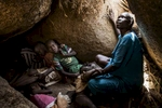 Africa, Sudan, South Kordofan. 07th Dec 2013. Semma Kafi Gelem, 30 years old, pregnant of her eighth child, seeks shelter for her and her children, from an Antonov bomber flying over the area of Buram.Africa, Sudan, Kordofan Meridionale. 7 dicembre 2013. Semma Kafi Gelem, 30 anni, incinta dell'ottavo figlio, cerca riparo per lei e i figli, da un bombardiere Antonov che sorvola la zona di Buram.