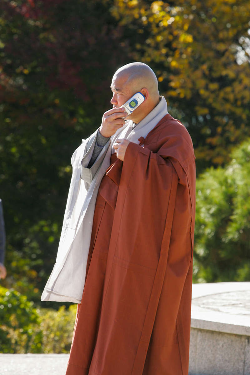President Bush, Laura Bush: Tour of Bulguksa Temple with President and Mrs. Moo Hyun Roh (Yang-Sook Kwon). Gyeongju, South Korea. Monk on cell phone.
