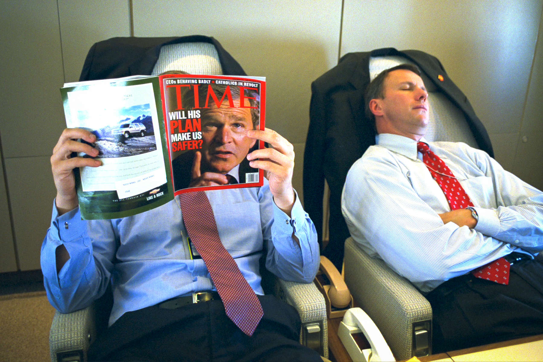 PRESIDENT BUSH DEPARTS FOR KANSAS CITY, MISSOURI. A staff member reads Time Magazine on Air Force One. President Bush's photograph is n the cover. A staff member sleeps.  Used in Bush Family Scrapbook June 1-June 20, 2002