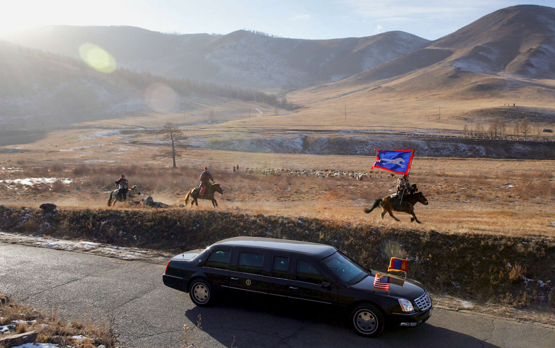 President Bush, Laura Bush: Presidential limousine, Mongolian horsemen en route Cultural event. Ikh Tenger, Herder Family Ger. Mongolia. Mongolian horsemen run with the motocade carrying President George W. Bush and Mrs. Bush to a cultural event in Ikh Tenger, Mongolia Monday, Nov. 21, 2005. The stop in Mongolia was the final one for the Bushes in a 7-day visit to Asia. White House photo by Paul MorseJUMBO