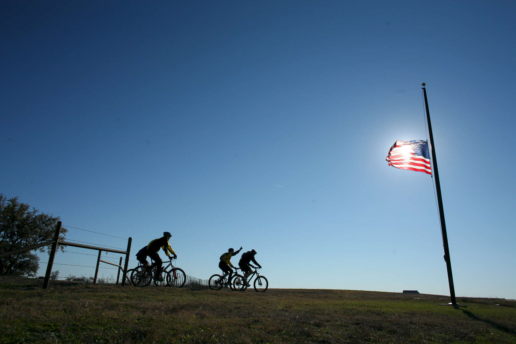President Bush: Bike Riding with guests. Ranch, Crawford, Texas. American flag at half-staff on death of President Gerald R. Ford. Participants include: Mark McKinnon, Craig Savage and Kia Baskerville. POW