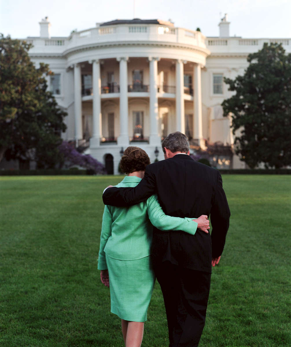 PRESIDENT BUSH AND LAURA BUSH HOLD HANDS AS THEY WALK ACROSS THE SOUTH LAWN TOGETHER DURING A PORTRAIT SESSION. THEY ARE ACCOMPANIED BY BARNEY AND SPOT. THE BUSHES POINT TO SPOT TO GET HER OUT OF THE PICTURE. THE BUSHES ARE PICTURED WITH THEIR ARMS AROUND EACH OTHER (SHOT FROM BEHIND).  MRS. BUSH TALKS ALONE WITH PHOTOGRAPHER SUSAN STERNER.RESTRICTEDLocation: SOUTH LAWN Bush Family Scrapbook 4.16.02-4.30.02