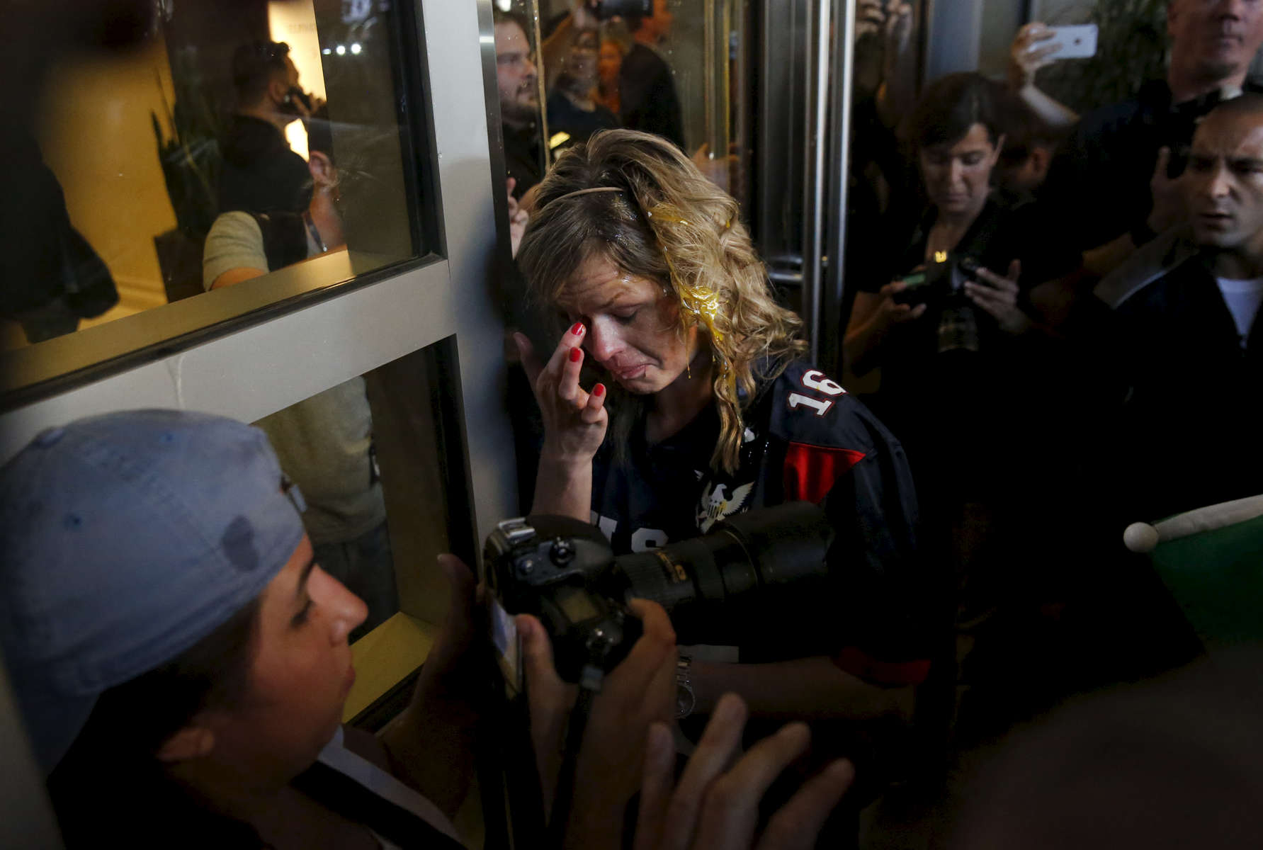 A Donald Trump supporter tries to clear her eyes after being cornered by an anti-Trump crowd and getting hit by multiple eggs near the convention center where presidential candidate Donald Trump held a campaign rally June 2, 2016 in downtown San Jose, Calif.