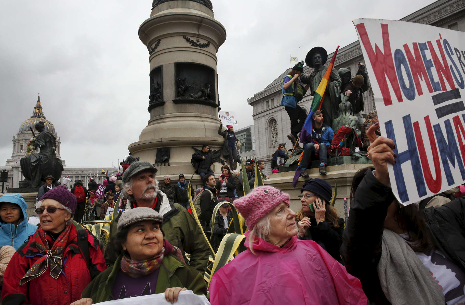 Elsy Tobar, front left, and Kathleen Holton, front right, stand with thousands of others and listen to speakers during a rally in Civic Center Plaza before the Women's March Jan. 21, 2017 in San Francisco, Calif. Thousands gathered in San Francisco to march in solidarity with the Women's March on Washington D.C. to protest the presidency of Donald J. Trump and to rally for the rights of all races, classes and gender identities.
