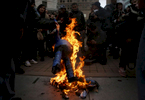 Protesters burn a Donald J. Trump piñata in Frank Ogawa Plaza during an anti-Trump protest on the evening of his presidential inauguration Jan. 20, 2017 in Oakland, Calif.