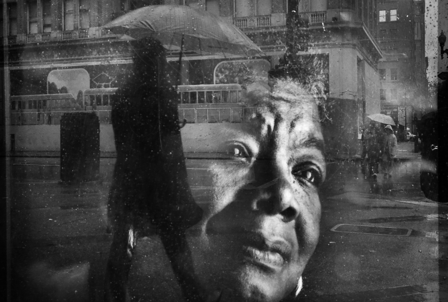 Pedestrians walk up and down Broadway Ave. in the rain as seen in a reflection on an ad featuring Maya Angelou Jan. 3, 2016 in downtown Oakland, Calif.