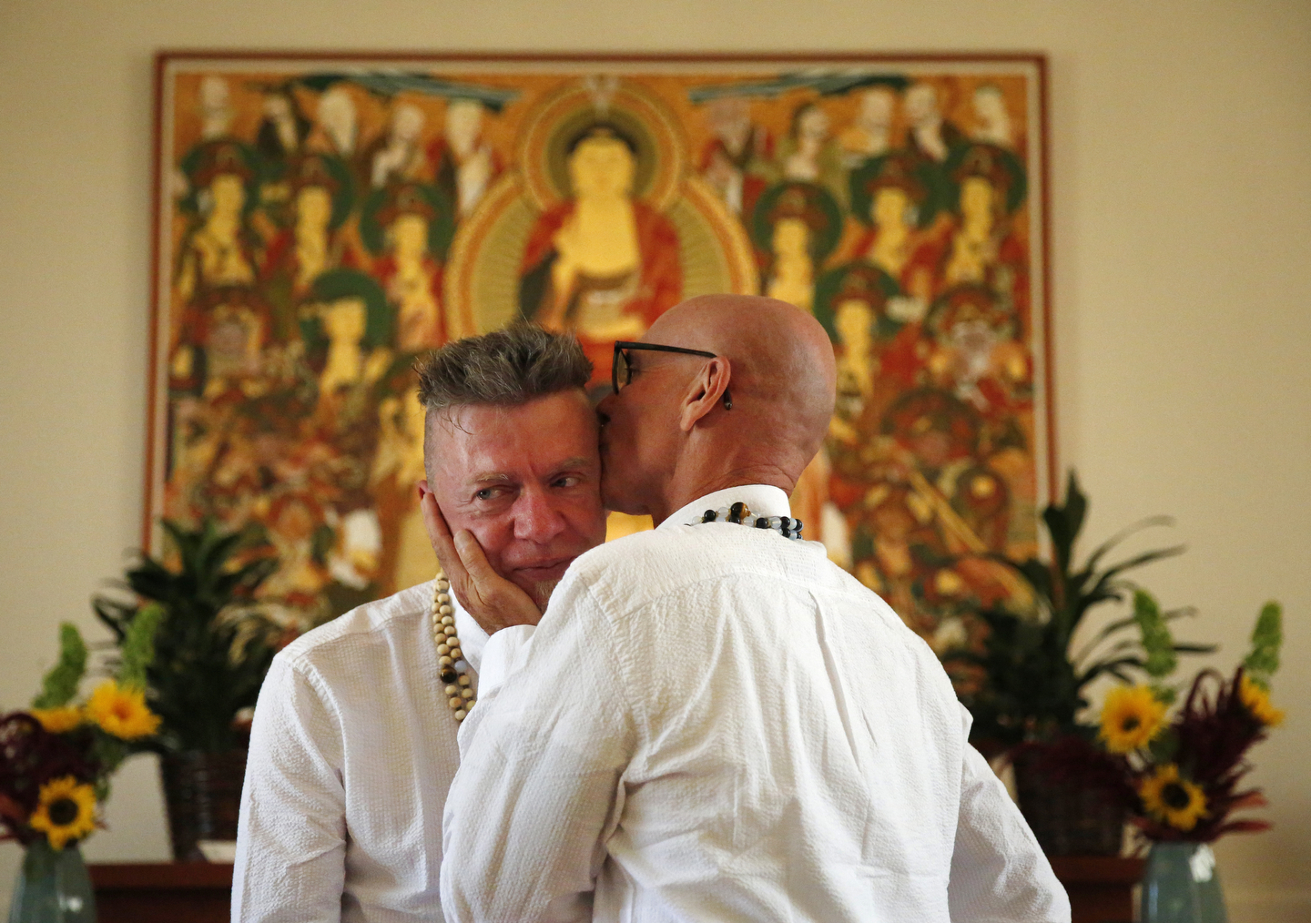 Ralph Thurlow kisses his husband David Spiher on the head at the end of their wedding ceremony at the Empty Gate Zen Center July 25, 2015 in Berkeley, Calif.