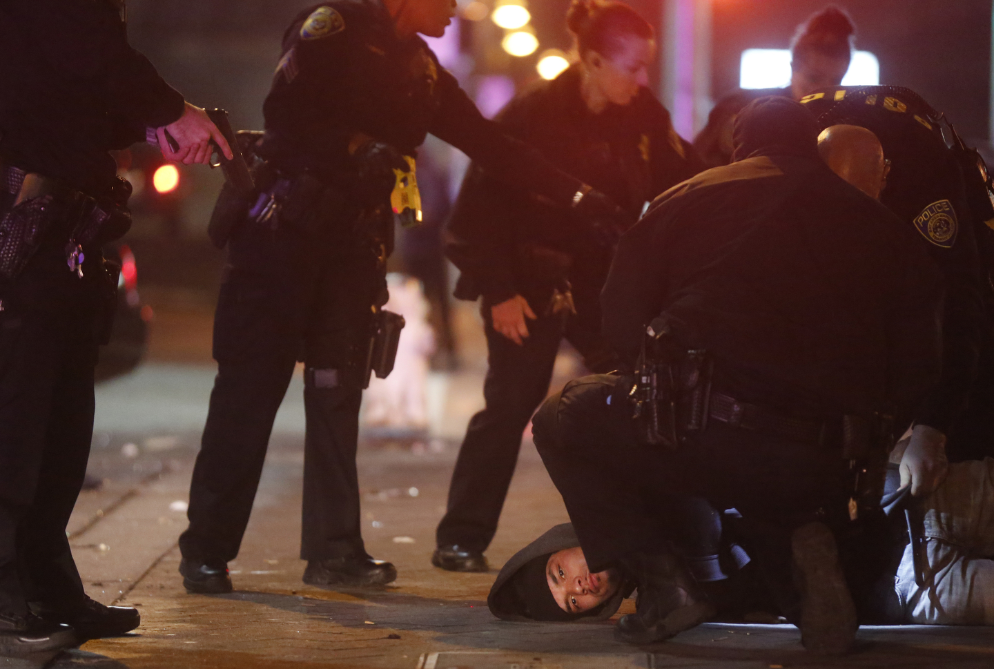 Police officers apprehend and search a suspect at a bus stop on 7th Street outside of the West Oakland BART station, the closest stop where there was a fatal shooting on a BART train Jan. 9, 2015 in Oakland, Calif.
